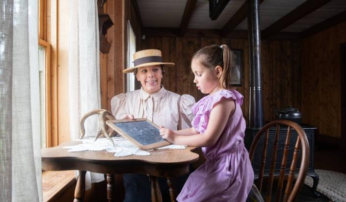 historically costumed interpreter helps young child to write on a slate